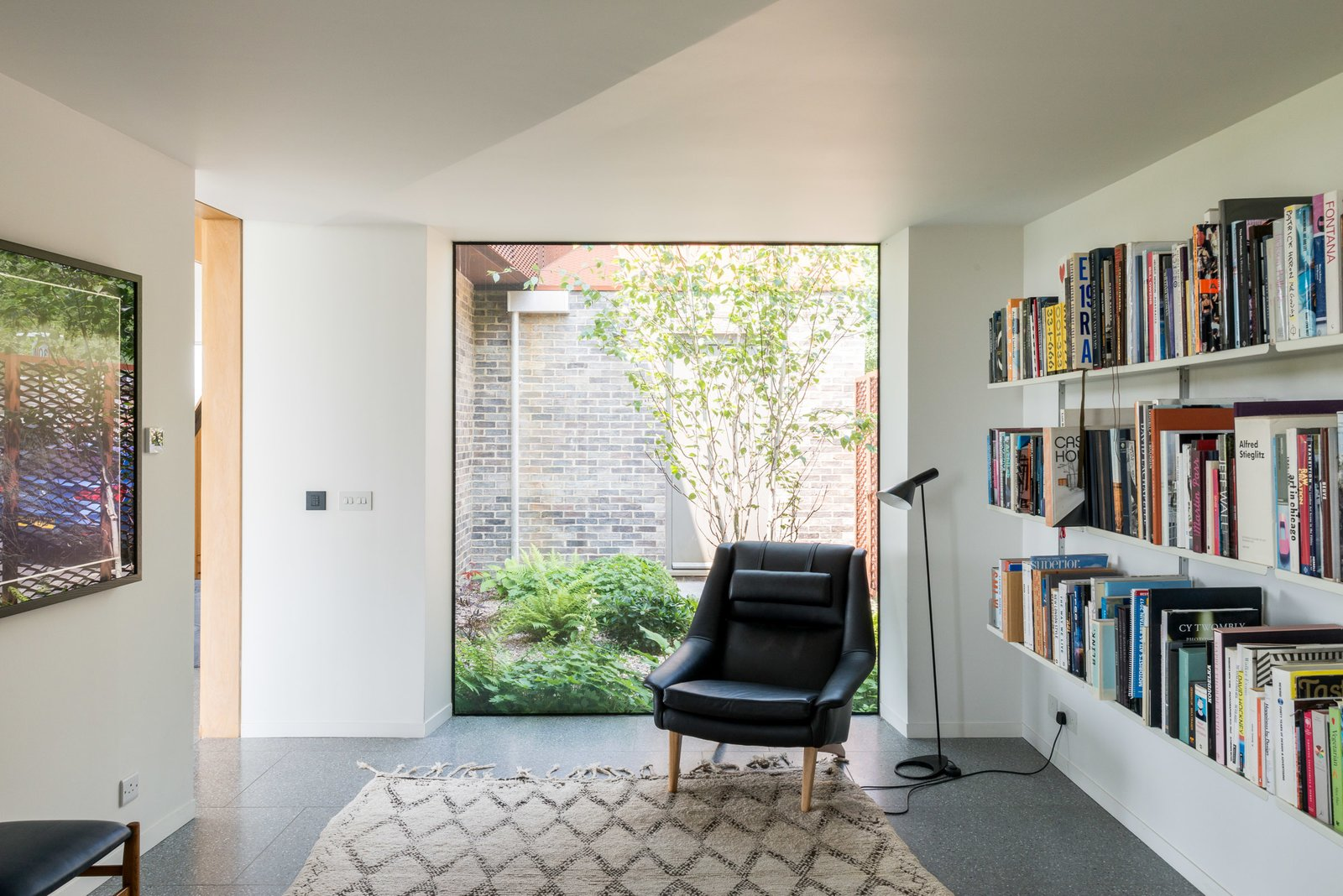 Tagged: Office, Library, Chair, Lamps, and Terrazzo Floor.  Photo 9 of 12 in Explore a Prefabricated House For Sale in England That's Clad With Cor-Ten Steel
