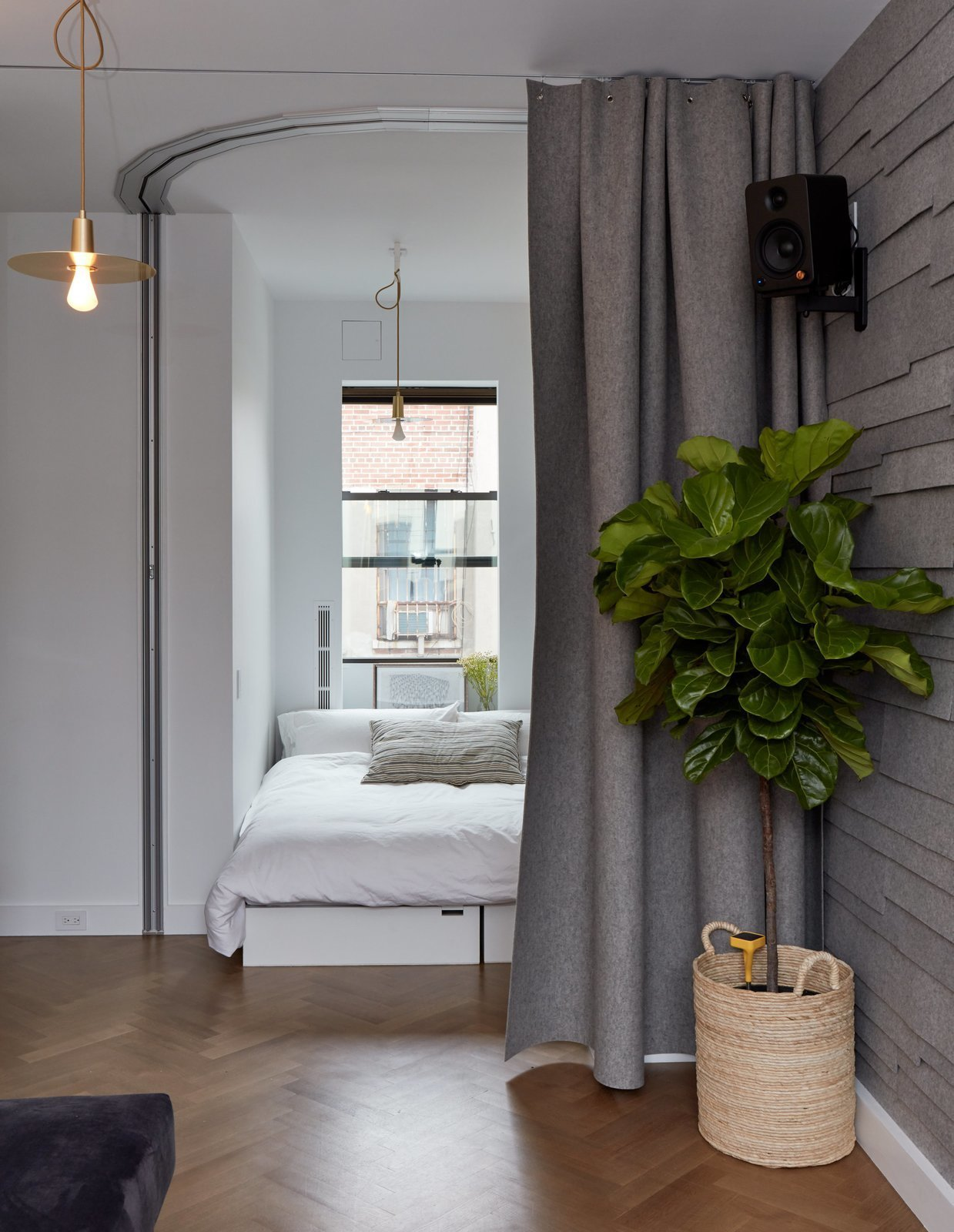 Small space champion Graham Hill's 350-square-foot apartment has an office that flips into a sleeping corner with seating cubes that can be arranged to form a bed and a curved Hufcor accordion door. Tagged: Bedroom, Medium Hardwood Floor, Bed, and Pendant Lighting.  Photo 6 of 11 in 11 Hidden Beds in Small Homes