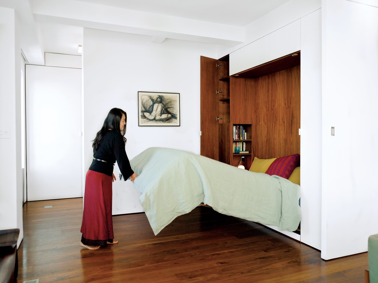 An architect couple uses multifunctional furniture and a hydraulic Murphy bed with secret compartments to keep the exterior walls uncluttered and achieve a clean and lean look in their 650-square-foot Chelsea apartment.