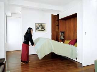 11 Hidden Beds in Small Homes - Photo 7 of 11 - An architect couple use multifunctional furniture and a hydraulic Murphy bed with secret compartments to keep the exterior walls uncluttered and achieve a clean and lean look in their 650-square-foot Chelsea apartment.
