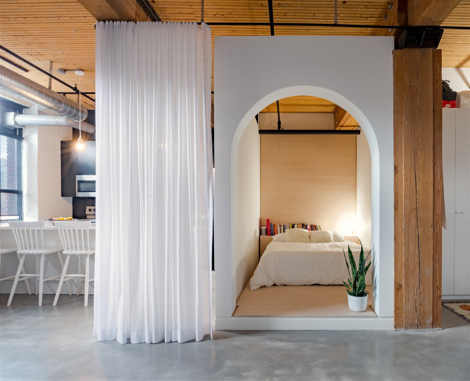 This small, L-shaped apartment has a bed box with an arched doorway with white walls and plywood finishings. Tagged: Bedroom, Bed, Table Lighting, and Concrete Floor.  Photo 11 of 11 in 11 Hidden Beds in Small Homes