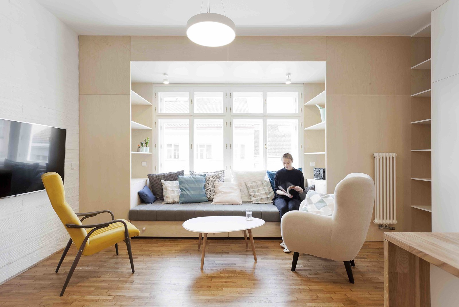 Tagged: Living Room, Chair, Sofa, Bookcase, Coffee Tables, Medium Hardwood Floor, Pendant Lighting, and Shelves.  Photo 1 of 13 in A Family Apartment in Prague That's Filled With Clever Storage Solutions and Built-In Nooks
