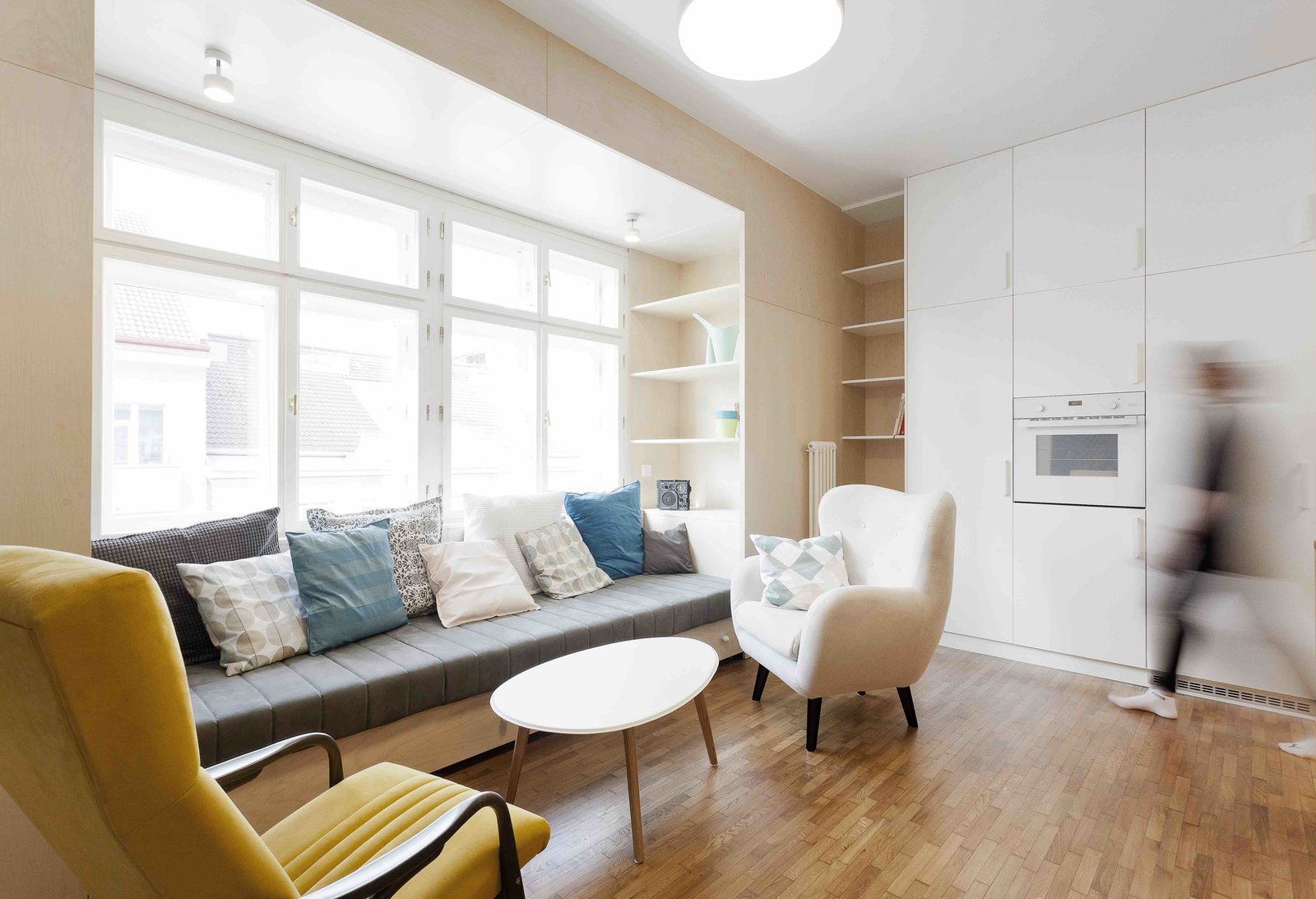 Tagged: Living Room, Coffee Tables, Storage, Chair, Sofa, Shelves, Medium Hardwood Floor, and Pendant Lighting.  Photo 3 of 13 in A Family Apartment in Prague That's Filled With Clever Storage Solutions and Built-In Nooks