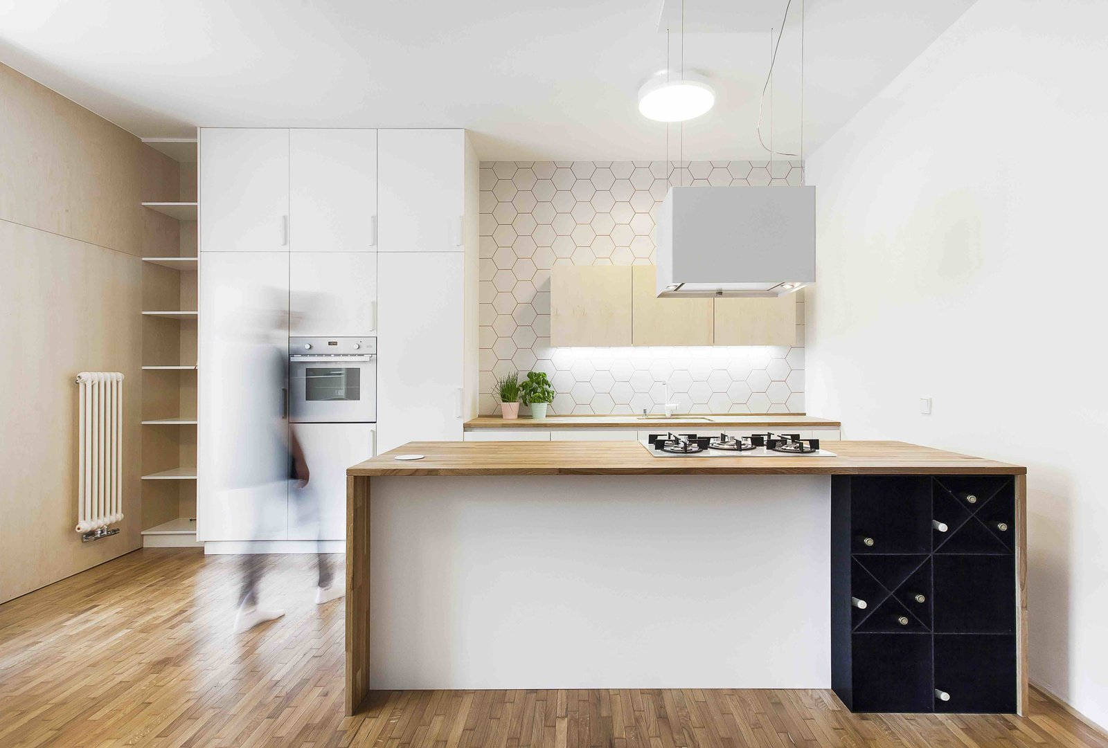 Tagged: Kitchen, White Cabinet, Medium Hardwood Floor, Wood Counter, Range, Ceiling Lighting, Range Hood, Wall Oven, Ceramic Tile Backsplashe, and Undermount Sink.  Best Photos from A Family Apartment in Prague That's Filled With Clever Storage Solutions and Built-In Nooks