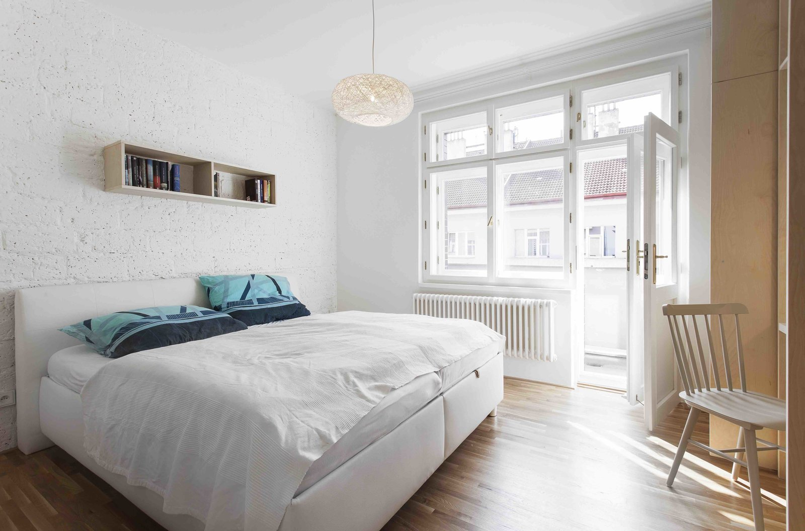Tagged: Bedroom, Bookcase, Medium Hardwood Floor, Pendant Lighting, Bed, and Chair.  Photo 6 of 13 in A Family Apartment in Prague That's Filled With Clever Storage Solutions and Built-In Nooks