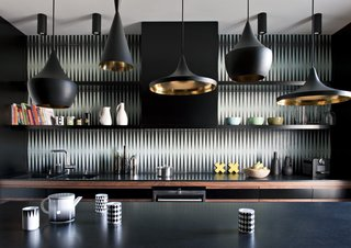 How to Design a Kitchen That's Ideal For Entertaining—and Shop Our Picks - Photo 7 of 9 - This dark and bold kitchen features Beat Pendants by Tom Dixon and a black-and-white tile backsplash by Popham Design.