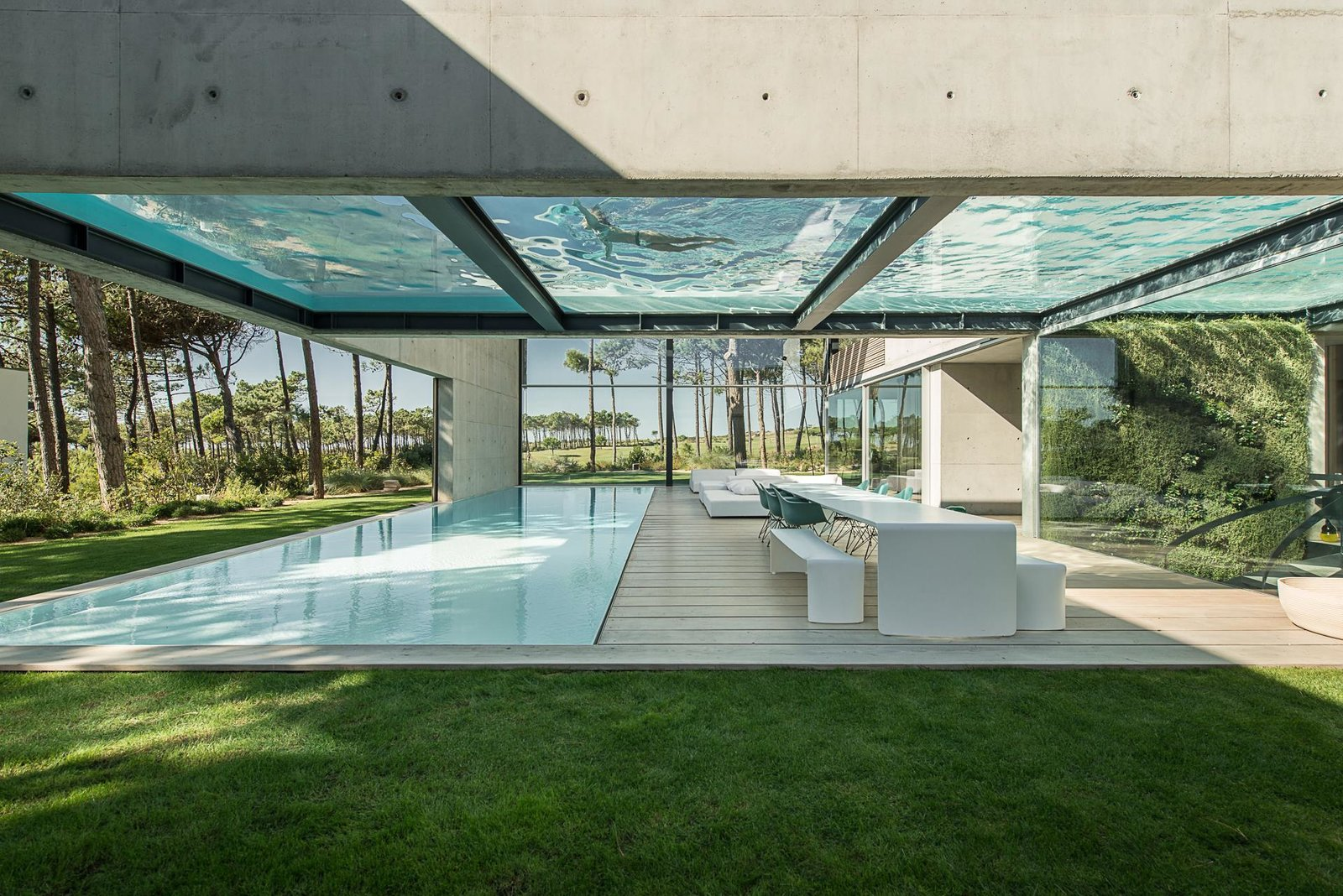 The Wall House in Cascais, a coastal town in an area known as the Portuguese Riviera, is an 11,840-square-foot home made with concrete, wood, and glass—and boasts a pair of large swimming pools on two levels.  Designed by José Guedes Cruz, César Marques, and Marco Marinho of the Portugal-based firm Guedes Cruz Architects, The Wall House is laid out in an open-box plan, and is fitted with plenty of glass windows to enhance the synergy between its interior and exterior spaces. Tagged: Outdoor, Back Yard, Trees, Grass, Large Pools, Tubs, Shower, Large Patio, Porch, Deck, Wood Patio, Porch, Deck, Swimming Pools, Tubs, Shower, and Plunge Pools, Tubs, Shower.  Photo 1 of 13 in A Pool With a Glass Bottom Hovers Over Another at a House in the Portuguese Riviera from 25 Modern Homes That Kill it With Concrete
