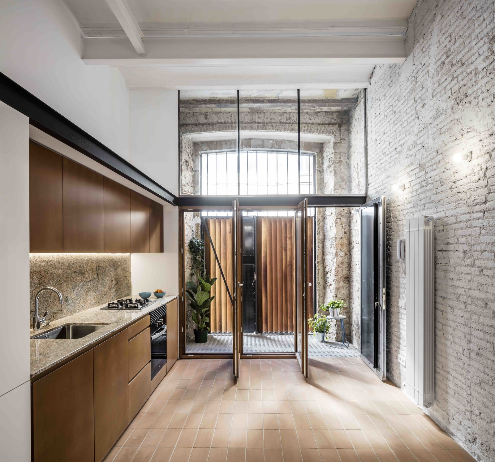 Tagged: Kitchen, Porcelain Tile Floor, Granite Counter, Wall Oven, Range, Accent Lighting, Wall Lighting, and Undermount Sink. This Double-Height Apartment in   Barcelona Features Historic Details and a Floating Staircase - Photo 5 of 13