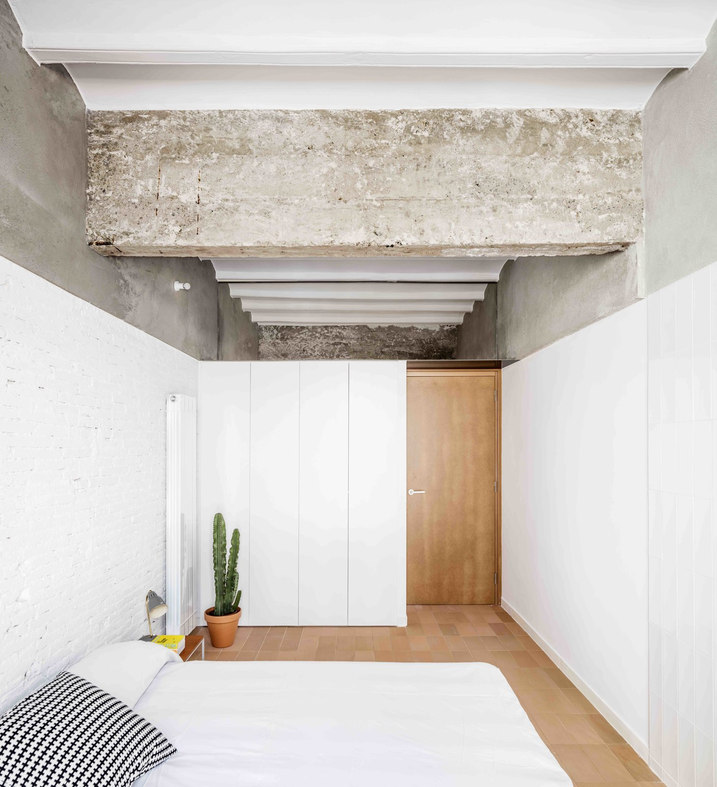 Tagged: Bedroom, Bed, Porcelain Tile Floor, Table Lighting, Wall Lighting, Storage, and Lamps.  Photo 8 of 13 in This Double-Height Apartment in   Barcelona Features Historic Details and a Floating Staircase