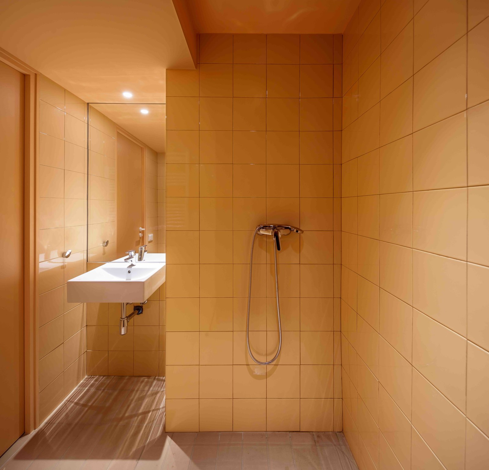 Tagged: Bath Room, Ceramic Tile Wall, Open Shower, Wall Mount Sink, and Ceiling Lighting.  Photo 11 of 13 in This Double-Height Apartment in   Barcelona Features Historic Details and a Floating Staircase