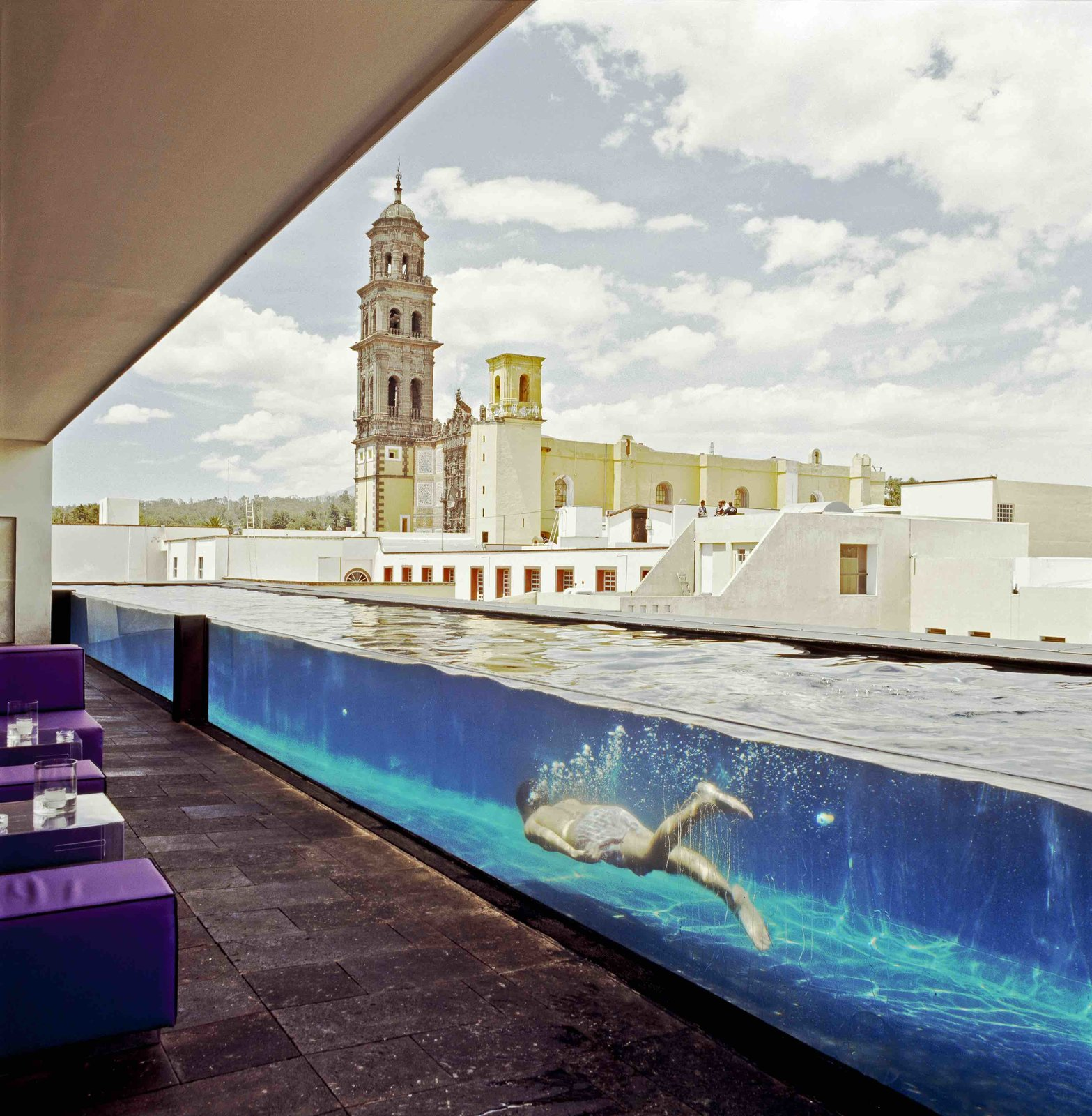 Modern furniture harmonizes with the old stone columns and walls of a former 19th century water purification factory in this Puebla boutique hotel. Archeological finds such as bottles and glass fragments for the old factory were incorporated into the interior design.