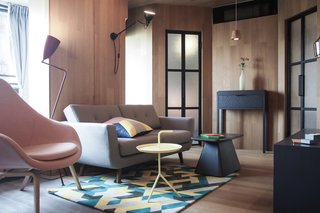 10 Small Apartments by a Hong Kong Design Studio That Are Less Than 1,000 Square Feet - Photo 5 of 10 - A colorful printed rug and matching cushion, a pink armchair, and plenty of bold geometric shapes give this apartment a slick, urban vibe.