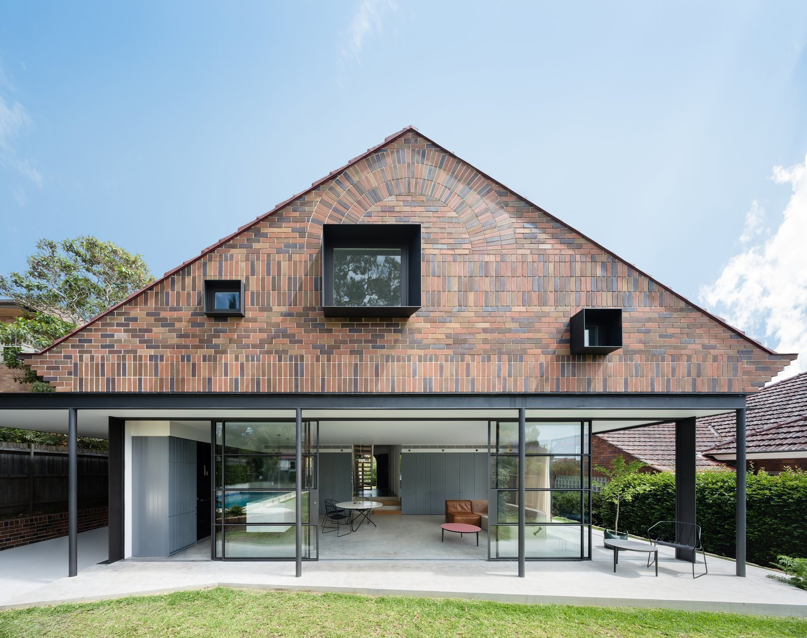 Bricks in five different colors, with alternating horizontal and vertical layouts create a visually captivating façade in this 1930s renovated bungalow in Sydney. 10 Modern Structures That Use Brick in Interesting Ways - Photo 4 of 10