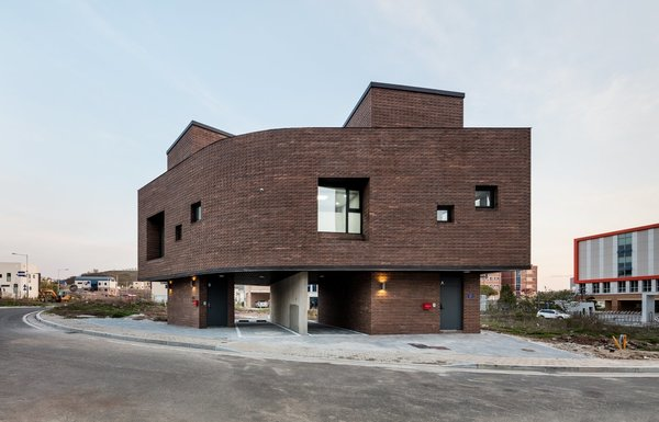 10 Modern Structures That Use Brick in Interesting Ways - Photo 7 of 10 - This home in Korea has a brick facade and interior walls that omit vertical construction joints. Instead, it's comprised of bricks that are stacked with an outward twist, which gives the facade a look that recalls the scales of a snake or a tree's bark.