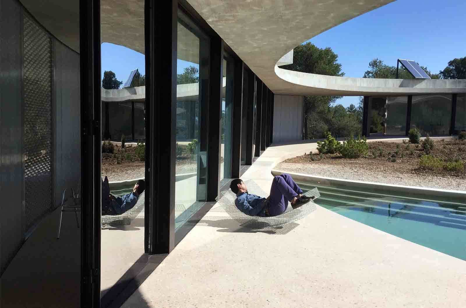 Tagged: Outdoor, Hardscapes, Shrubs, Concrete Patio, Porch, Deck, Large Patio, Porch, Deck, and Small Pools, Tubs, Shower.  Photo 7 of 9 in Stay in a Solar-Powered, Ring-Shaped Vacation Home in the Spanish Countryside