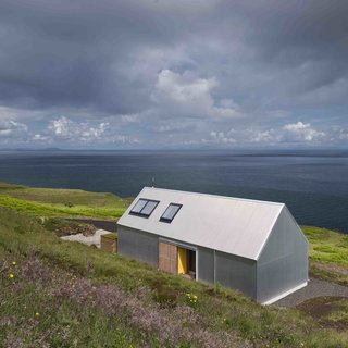 "Dwell's Top 10 Vacation Homes of 2017 - Photo 2 of 10 - On the northwestern tip of Scotland's Isle of Skye is a vacation rental that's inspired by the region's traditional ""crofter style"" cottages, but covered with a skin of tin.  Designed and built by Gill Smith and Alan Dickson of Scottish practice Rural Design Architects, this house sits along the rugged Isle of Skye coast and has a rudimentary form that recalls children's drawings of pitched-roof homes."
