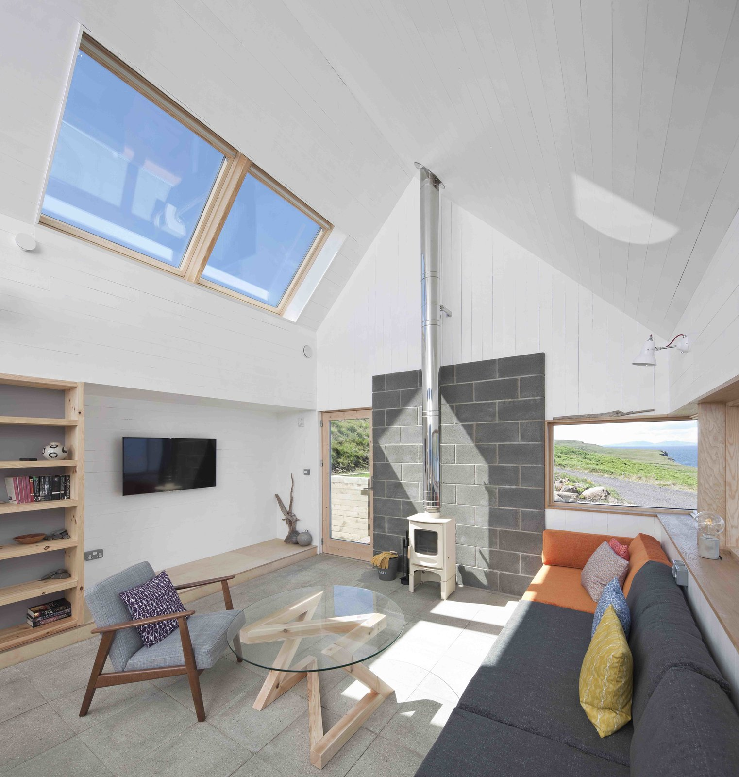 Tagged: Living Room, Sofa, Coffee Tables, Shelves, Chair, Concrete Floor, Bookcase, Wall Lighting, and Wood Burning Fireplace.  Photo 2 of 11 in Stay in a Modern Tin Cottage on Scotland's Isle of Skye