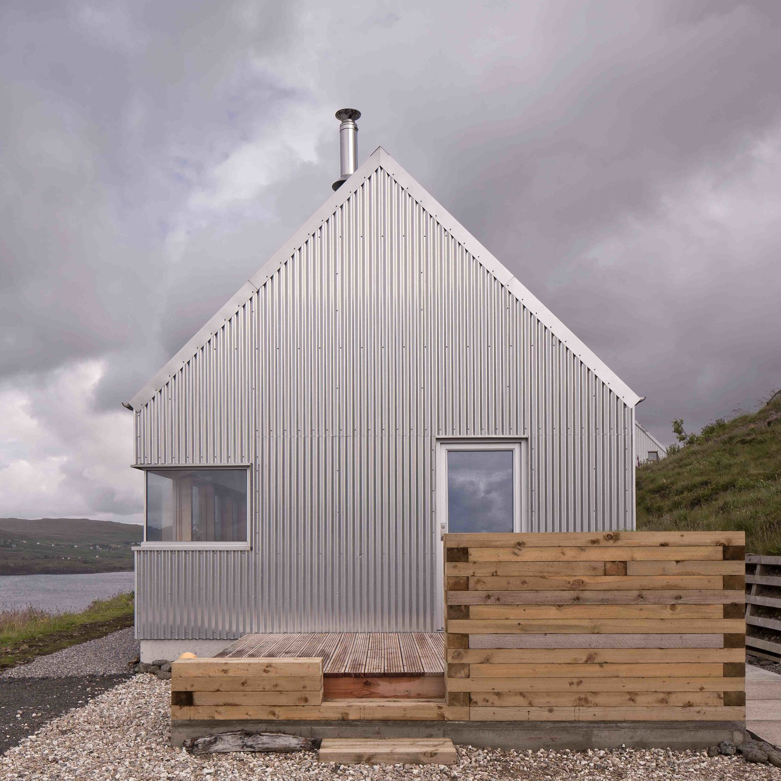 Tagged: Outdoor, Side Yard, Wood Patio, Porch, Deck, Grass, Small Patio, Porch, Deck, Horizontal Fences, Wall, and Wood Fences, Wall.  Photo 3 of 11 in Stay in a Modern Tin Cottage on Scotland's Isle of Skye