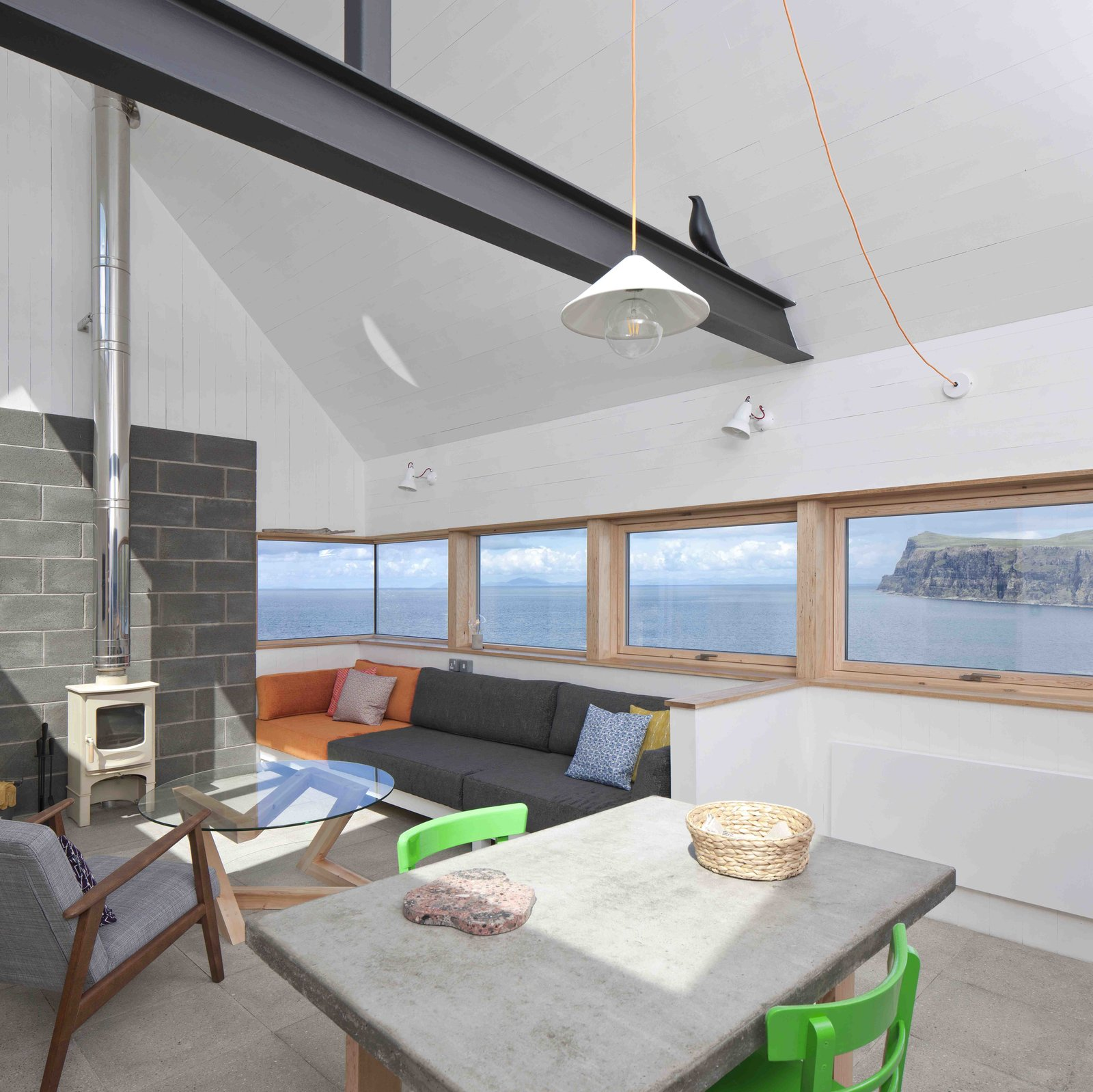Tagged: Living Room, Coffee Tables, Table, Chair, Sofa, Pendant Lighting, Wall Lighting, Concrete Floor, and Wood Burning Fireplace.  Photo 4 of 11 in Stay in a Modern Tin Cottage on Scotland's Isle of Skye