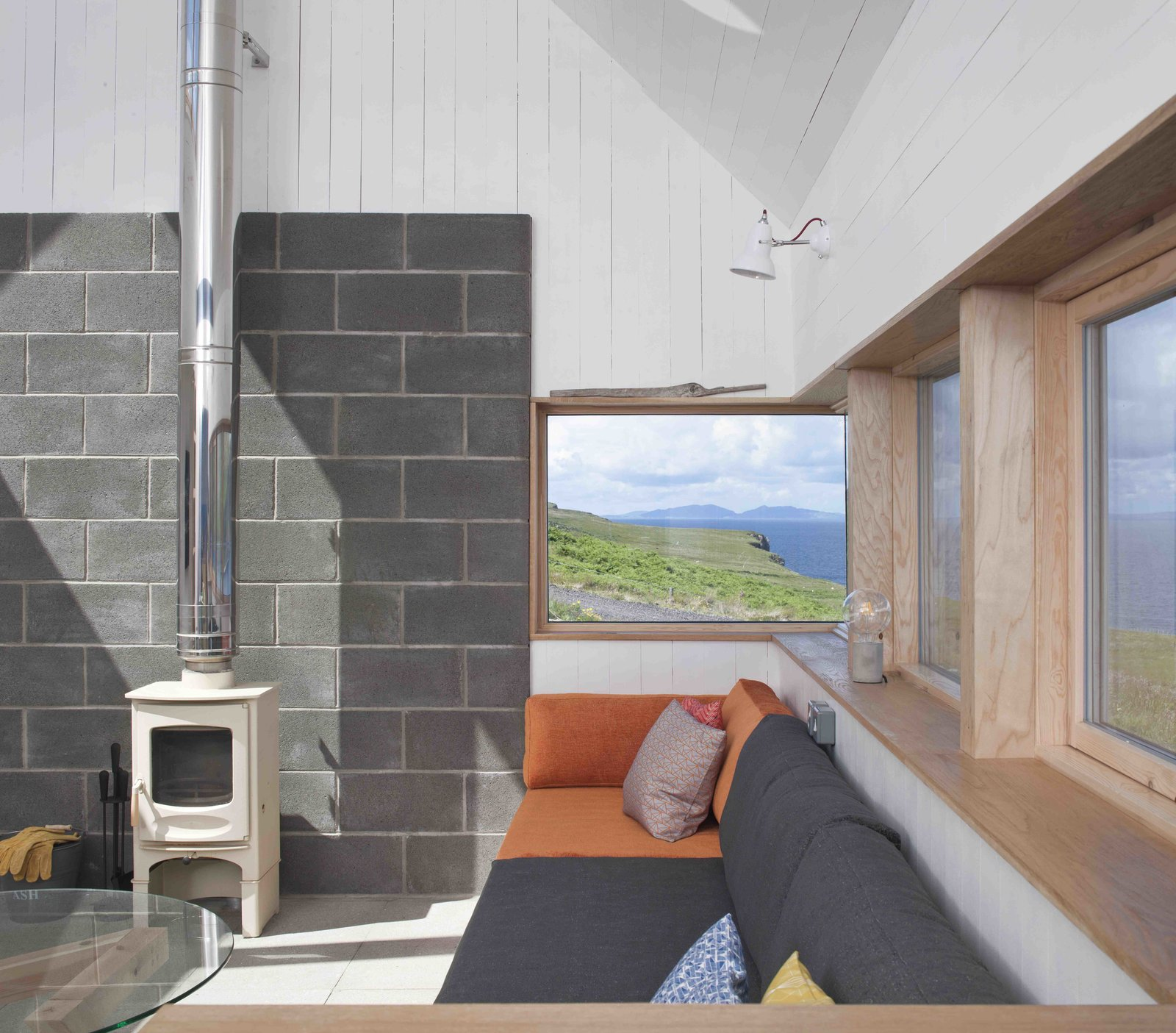 Tagged: Living Room, Coffee Tables, Wall Lighting, Sofa, Wood Burning Fireplace, and Concrete Floor.  Photo 9 of 11 in Stay in a Modern Tin Cottage on Scotland's Isle of Skye