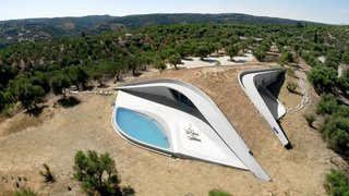 8 Subterranean Homes That Are Out of This World - Photo 5 of 8 - Embedded into the top of a hill, Villa Ypsilon in the Greek seaside village of Messenia has a Y-shaped, earth-covered roof promenade that looks as if it's an extension of the terrain.