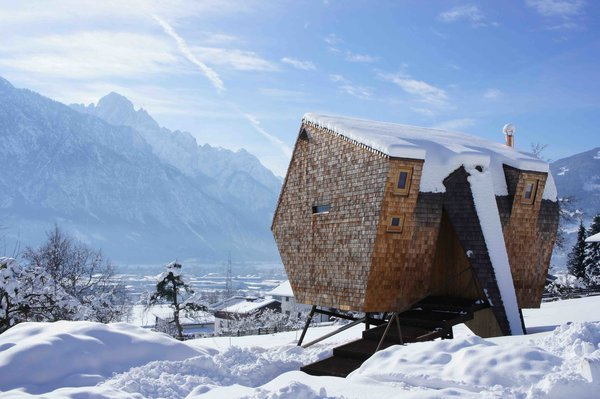Next to an old farmhouse in the East Tyrolean village of Nussdorf, Austria, is an unusually shaped, shingle-clad cabin that's raised up on skinny steel struts.   Set on a hilly incline and designed by architects Peter and Lukas Jungmann, the cabin appears to hover above ground like some sort of alien object—a stark contrast to its pastoral environment and the traditional Austrian chalets that surround it.   Because of its irregular, otherworldly form, and how it seems to be suspended in midair, the cabin was named