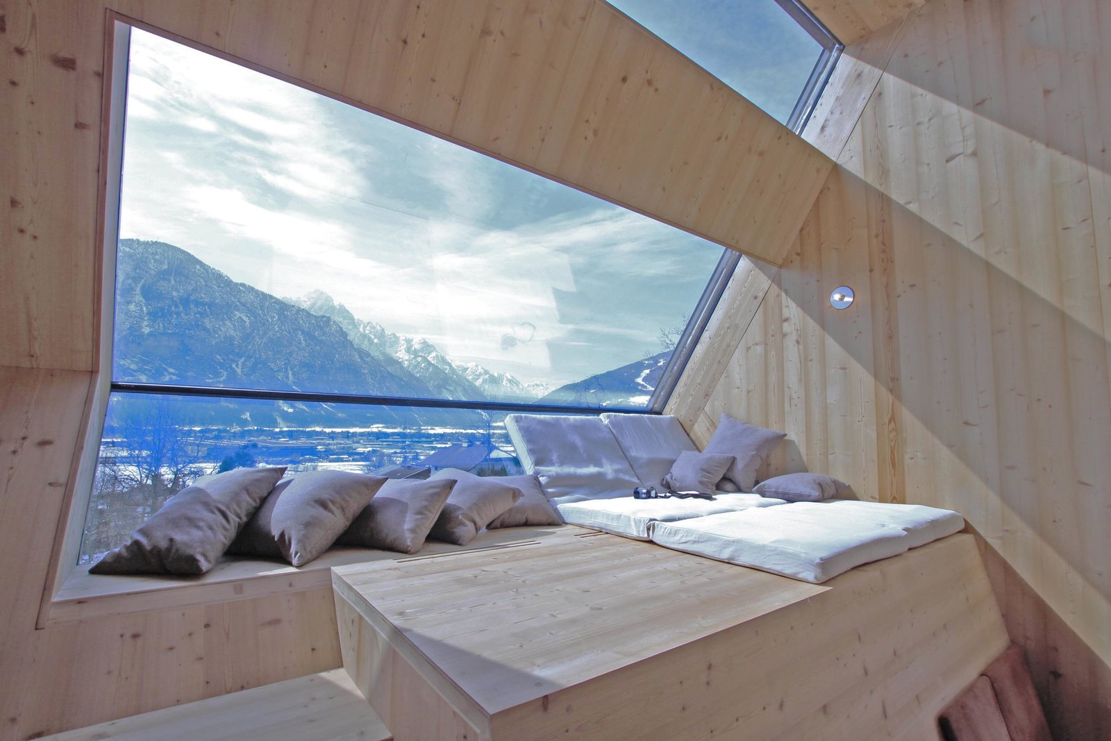 Fitted with waterproof and rot-resistant larch wood and large, angled-glass windows, the interior has a warm, sci-fi-inspired feel and gets flooded with sunlight during the day.