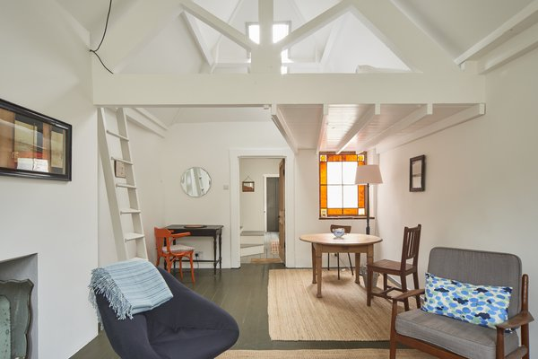 The quaint living space features a stained-glass window, lofted sleeping platform, vaulted ceilings, and arched-sash windows.