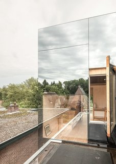 "8 Structures and Spaces That Use Mirrored or Reflective Surfaces in Interesting Ways - Photo 8 of 8 - With an extension clad in mirrored glass that reflects the silhouettes of the existing brick house, ""Mirror Mirror"" is a home that shields its residents from view during the day, but exposes the extension's interiors at night."