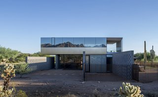 8 Structures and Spaces That Use Mirrored or Reflective Surfaces in Interesting Ways - Photo 1 of 8 - Szu-Ping Patricia Chen Suchart and Thamarit Suchart of Chen + Suchart Studio used brushed-stainless steel and glass on the upper volume of this Sonoran Desert home. The glass, which was treated with a thermal coating, provides protection from the sun and creates a surface with a silvery, mirrored effect that captures the colors of the desert and mountain peaks.