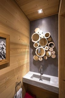 8 Structures and Spaces That Use Mirrored or Reflective Surfaces in Interesting Ways - Photo 4 of 8 - Nature is present throughout the interiors of this French Alpine home, including in the bathroom, where the cross section of tree trunks serve as frames in a cluster of small mirrors.