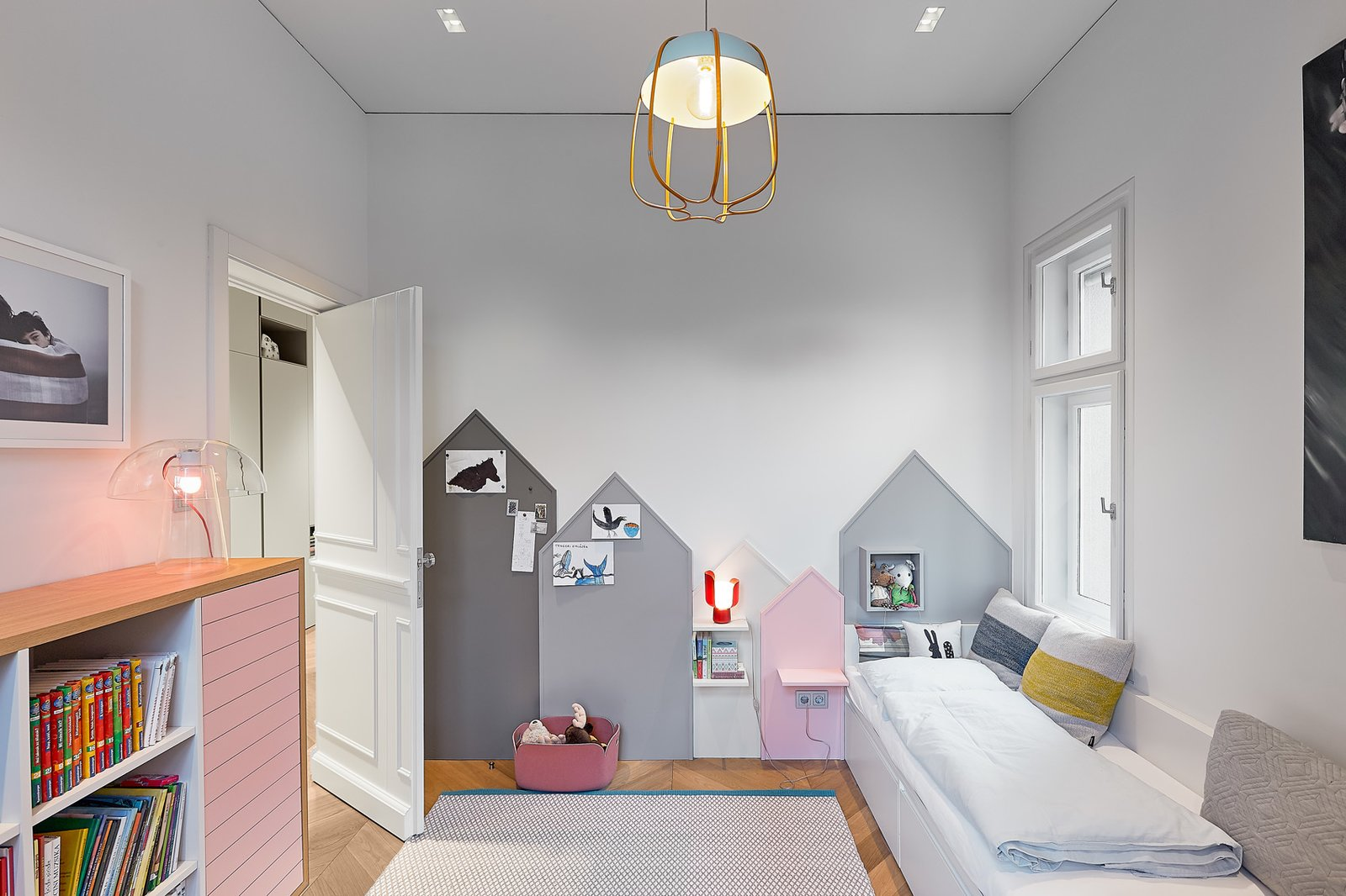 Tagged: Kids, Playroom, Bedroom, Storage, Shelves, Lamps, Light Hardwood, and Rug.  Best Kids Photos from A Family Villa in Budapest With Colorful, 1960s-Inspired Interiors