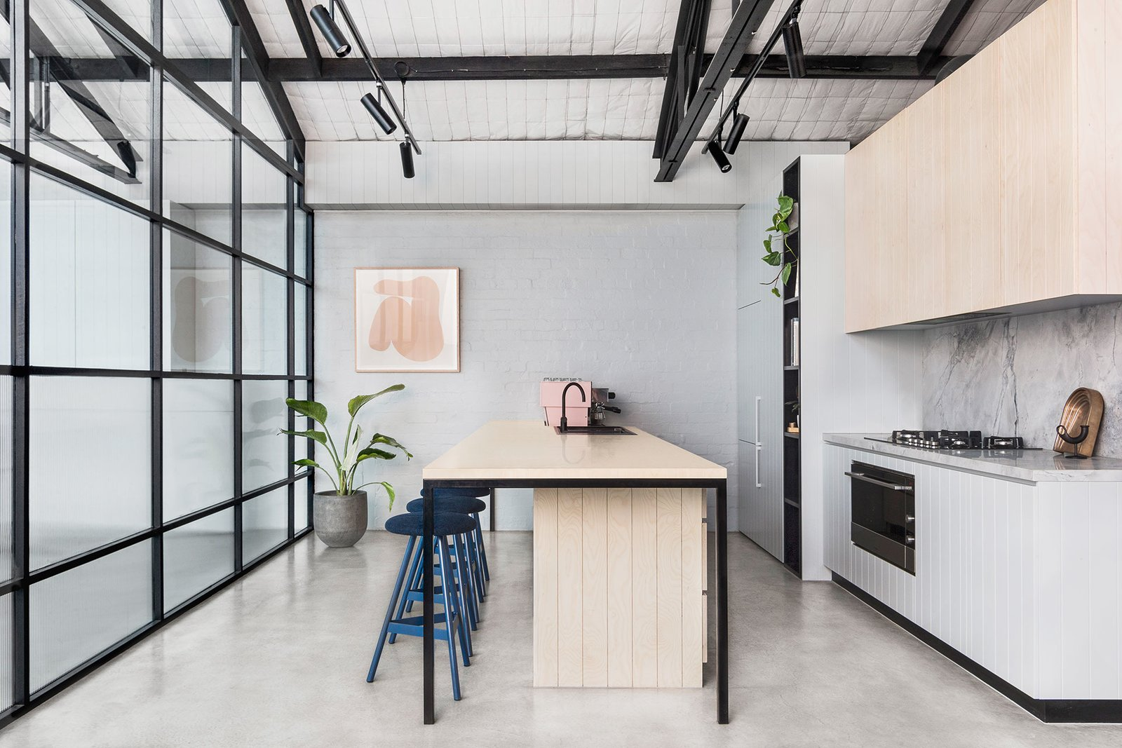 Tagged: Kitchen, Marble Counter, Wood Cabinet, Concrete Floor, Track Lighting, Wall Oven, Range, Drop In Sink, and Marble Backsplashe.  Photo 12 of 14 in An Art Deco Warehouse in Melbourne Is Converted Into a Shared Office Space