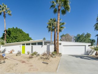 Experience A Blast From The Past At One Of These Midcentury-Modern Palm Springs Vacation Homes - Photo 6 of 8 - This vacation home in the Racquet Club North neighborhood has an eye-catching citrus-hued front door, and a living area that makes the most of the Californian sunshine with a wall of glass.