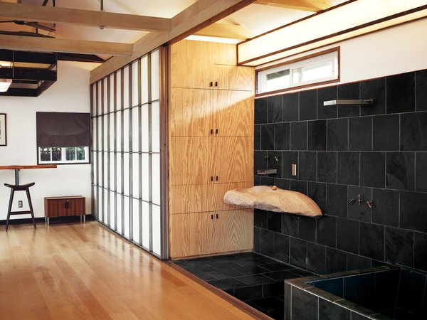 """In the bathroom of """"Mad Men"""" actor Vincent Kartheiser's """"Japanese-inustrial style"""" Hollywood home is an irregular-shaped sink of raw stone adjacent to the shower and soaking tub."""