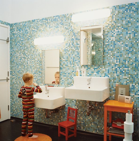 In the tiled master bathroom of their L.A. Chinatown loft, Dan Bernier and Amy Finn Bernier have an child-height vanity next to an adult sized vanity. A clever to impart good oral hygiene habits to little ones.