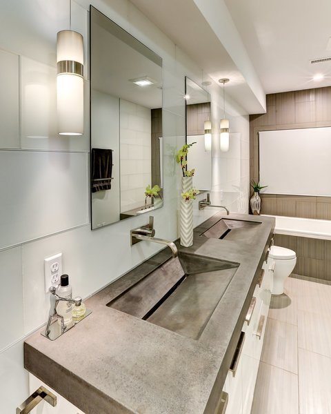 The master bathroom of this North Carolina home features very contemporary, custom made concrete countertop with integrated trough sinks.