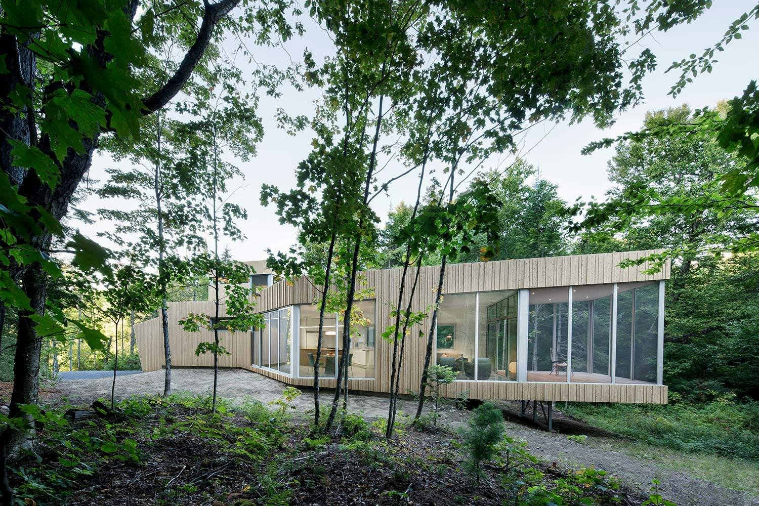 7 Incredible Modern Homes by Canadian Architect Paul Bernier - Photo 2 of 7 - The facade will turn gray and silver naturally, so its verticality, texture, and colors will blend in with the vertical tree trunks of the forest.