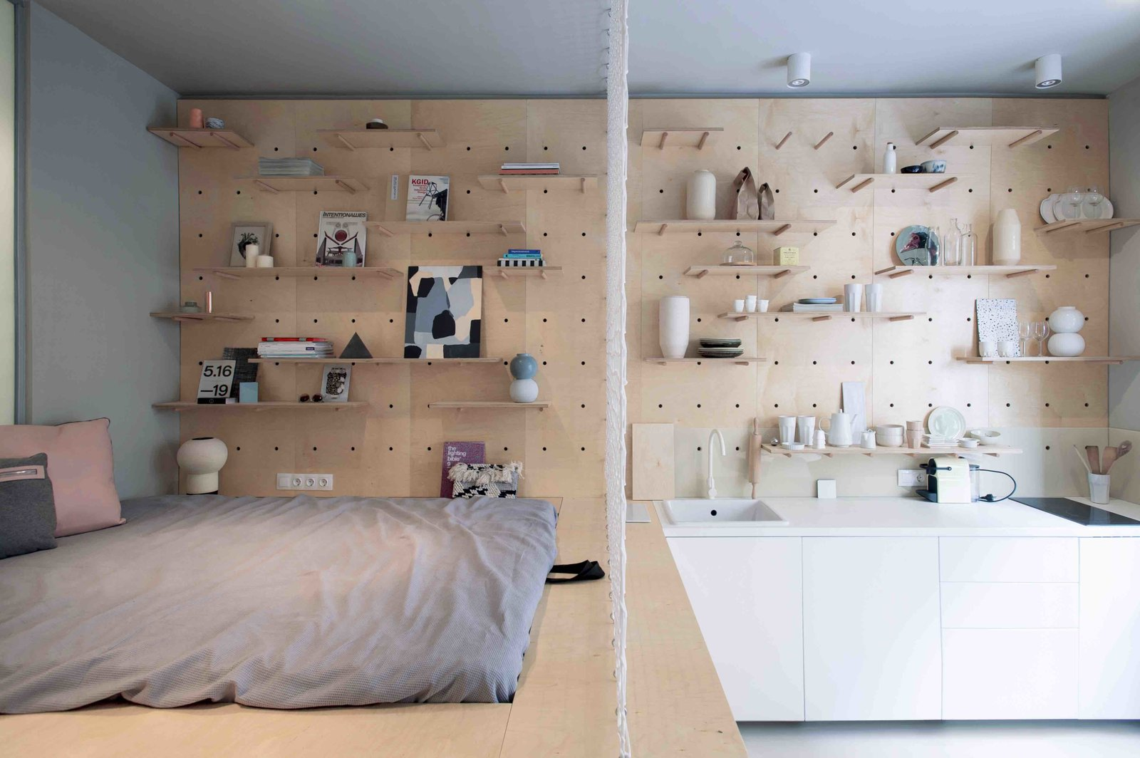Budapest design studio POSITION Collective employs clever storage solutions, including a wardrobe rack, modular walls, and a storage-filled bed, in order to maximize functional space.  Though the 323-square-foot studio is now being leased out on a long-term basis, the clients had originally wanted to turn the small apartment into a stylish and memorable space for design-loving travelers visiting Budapest. Tagged: Bedroom, Bed, Storage, Ceiling Lighting, and Shelves.  Best Photos from 3 Smart Storage Systems Maximize Space in a Tiny Studio Apartment in Budapest