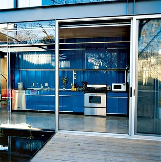 9 Great Kitchen Cabinet Ideas - Photo 8 of 9 - If you're a minimalist, you may prefer hingeless track doors over swinging doors with handles. In this steel-frame Texas home, the bright blue galley-style kitchen has no visible hinges, which makes it look like it's one with the similar-colored back wall.