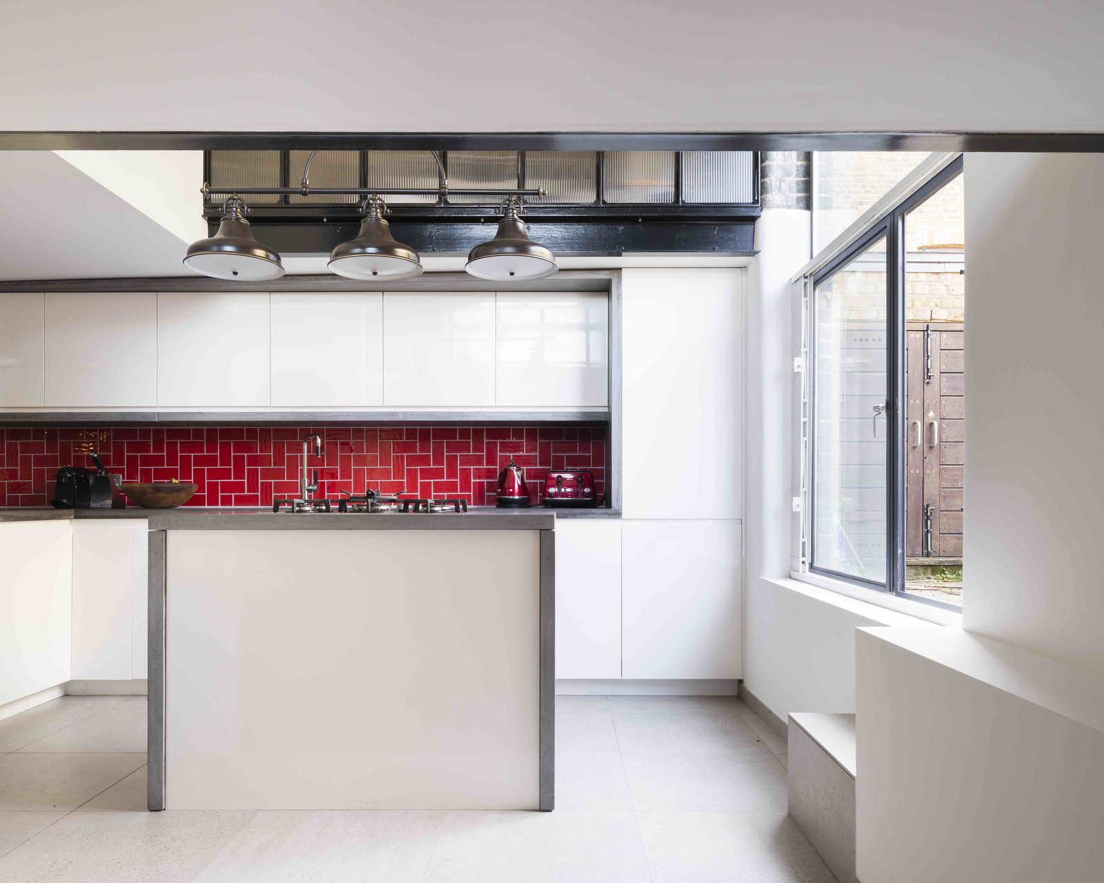 Tagged: Kitchen, Concrete Counter, White Cabinet, Ceramic Tile Floor, Subway Tile Backsplashe, Pendant Lighting, Refrigerator, Range, and Drop In Sink.  Photo 6 of 12 in An Old Grain Warehouse on the River Thames Is Transformed Into an Industrial-Modern Home