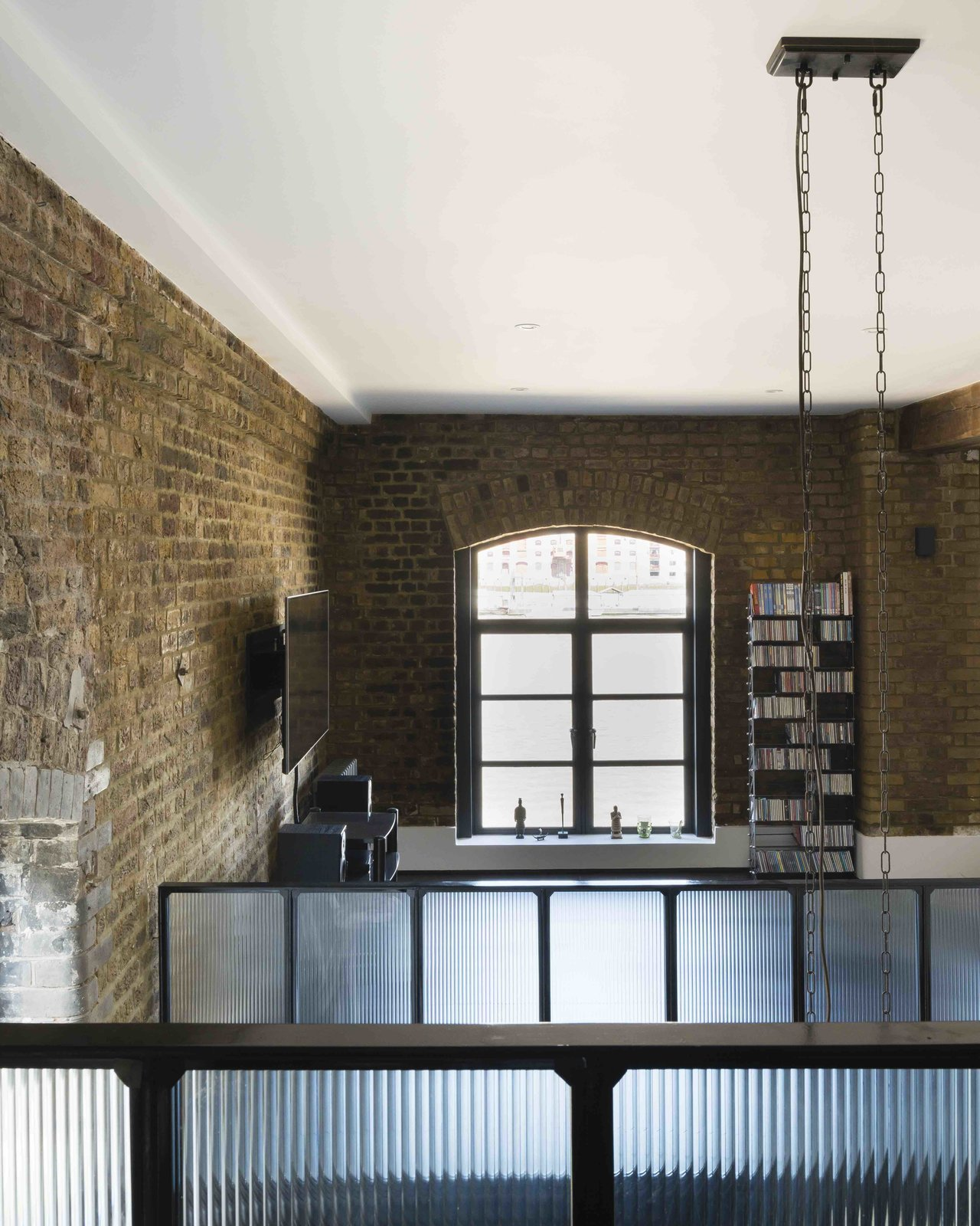 Tagged: Living Room and Bookcase.  Photo 4 of 12 in An Old Grain Warehouse on the River Thames Is Transformed Into an Industrial-Modern Home