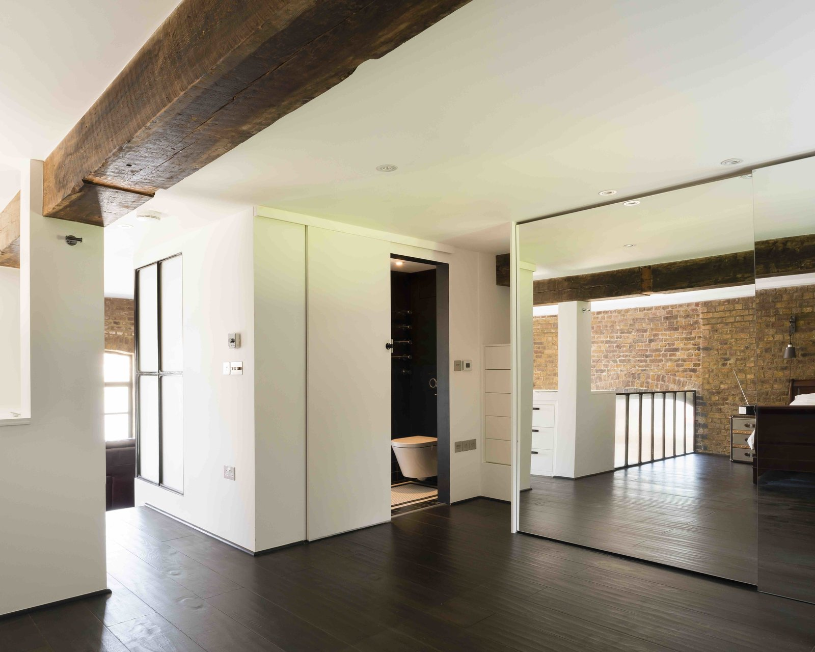 Tagged: Bedroom, Dark Hardwood Floor, Ceiling Lighting, Recessed Lighting, Wardrobe, and Dresser.  Photo 8 of 12 in An Old Grain Warehouse on the River Thames Is Transformed Into an Industrial-Modern Home
