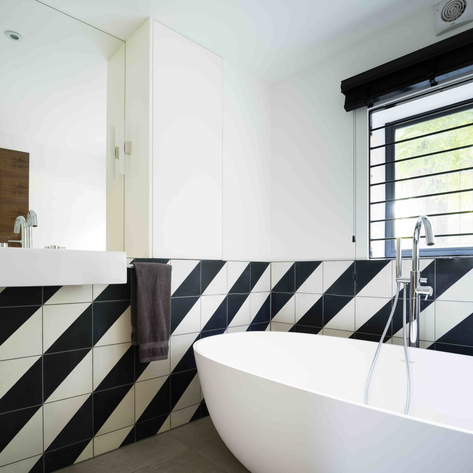 Tagged: Bath Room, Freestanding Tub, Wall Mount Sink, and Ceramic Tile Wall.  Photo 10 of 12 in An Old Grain Warehouse on the River Thames Is Transformed Into an Industrial-Modern Home