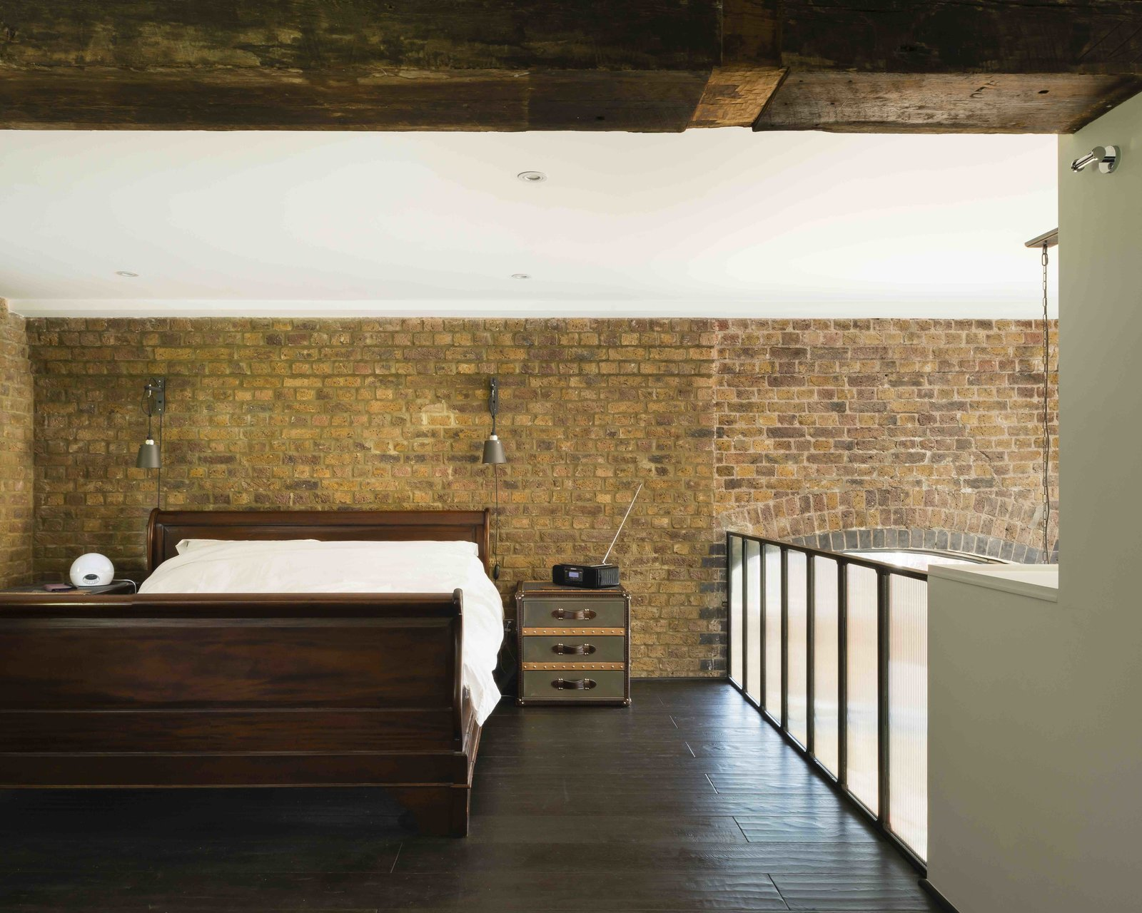 Tagged: Bedroom, Bed, Night Stands, Wall Lighting, Ceiling Lighting, Recessed Lighting, and Dark Hardwood Floor.  Photo 11 of 12 in An Old Grain Warehouse on the River Thames Is Transformed Into an Industrial-Modern Home