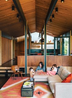 7 Colors to Use in Your Home to Create a Midcentury-Modern Look With a Twist - Photo 6 of 7 - To balance out bright reds, oranges, or yellows, try pewter grays, which can add a little cool to warmer color schemes. In this updated 1950s Portland home, a light gray Neo sofa by Bensen harmonizes with warm wooden walls, ceilings, and floors, as well as a red-and-mustard yellow vintage rug. If you're thinking of gray for your walls or ceilings, Wright Soft Gray (FLLW872) from PPG Pittsburgh Paints is a versatile option.