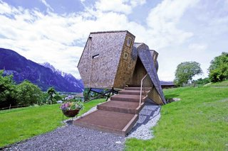 These 9 Structures Prove That Shingle Exteriors Can Be Surprisingly Modern - Photo 1 of 9 - Designed by architects Peter and Lukas Jungmann, this holiday cabin near an old farmhouse in the East Tyrolean village of Nussdorf, Austria, is covered in rustic Austrian-style shingles. Its sharp angles and asymmetrical shape gives it a distinctly futuristic, UFO-like appearance.