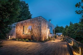 These 9 Structures Prove That Shingle Exteriors Can Be Surprisingly Modern - Photo 3 of 9 - Inspired by bird hides, this annex building in Cornwall, England, that was part of an existing thatch cottage was fully revamped with concrete and silver-wood shingles to create a minimalist rental cottage.
