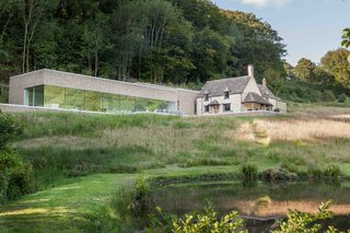 9 Traditional-Turned-Modern Cottages You Can Rent in the UK - Photo 2 of 9 - Sitting on a peaceful property within a 16-acre wooded valley near Cheltenham, The Find is a minimalist stone house with a new elongated extension that includes light concrete interiors and walls of glass windows.