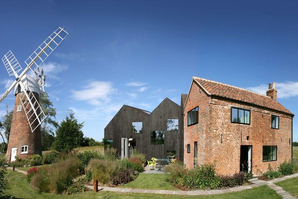 This sensitively restore old mill keeper's cottage on the bank of Norfolk's River Ant has a new addition made from solid laminated wood that is a shadow of the original cottage.